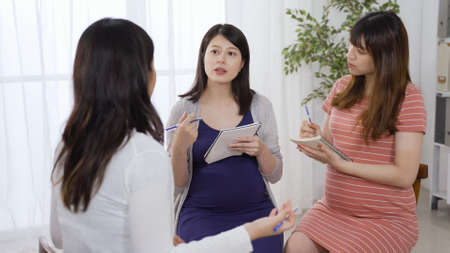 three asian beautiful pregnant moms holding notes are exchanging ideas while listening to their teammates sharing. Reklamní fotografie