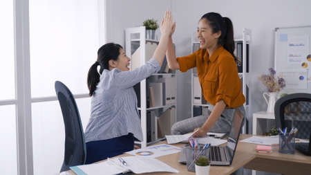 two fashion asian japanese female business woman giving a high five gesture while they laughing and cheering success