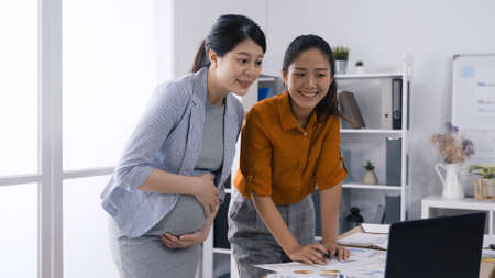 elegant korean woman employee in orange shirt is reporting company marketing analysis to her boss while standing in modern office