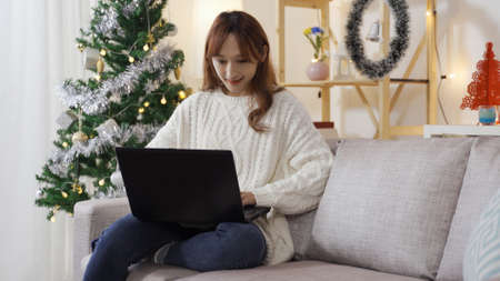 charming asian chinese woman sitting on sofa with laptop is searching boxing day sale on the internet at home.