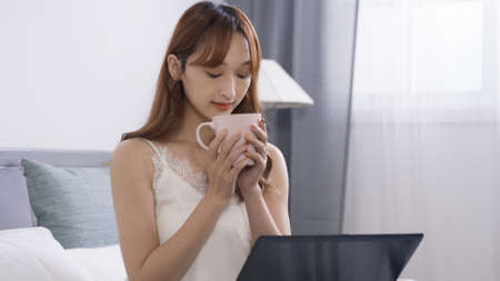 portrait charming asian japanese woman in white nightdress sipping and smelling cup of morning coffee during leisure time with herself at home.