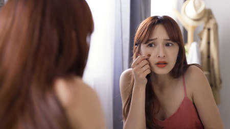 frowning asian japanese young female looking into mirror is unhappy about finding fine lines around eyes in the morning