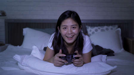front view asian lady staring at screen and playing racing game with concentration while lying in bedroom in late night.