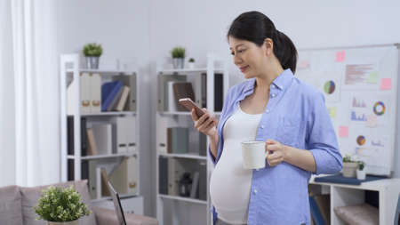 chinese pregnant female business owner in casual wear standing in the home studio with smartphone and cup of coffee.