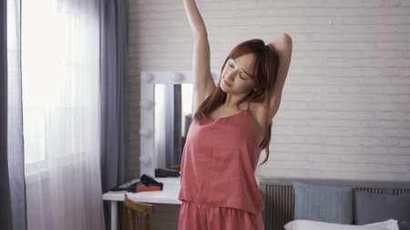 attractive asian japanese girl in a nightgown standing by window with sunshine and stretching body slowly. Reklamní fotografie