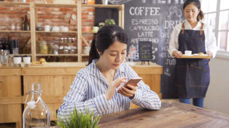 Portrait of office lady using her mobile phone in cafe bar while waiting ordered meal. young girl waitress in apron walking in back carrying tray with coffee and croissant. good service concept Reklamní fotografie