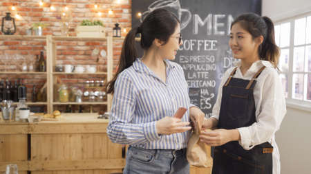 small business people and service concept. female bartender serving customer at coffee shop. waitress giving paper bag with meal takeaway in cafe bar while client leaving and holding smartphone