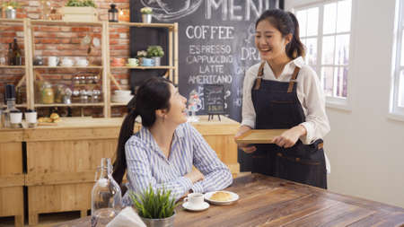 Young asian busiensswoman relax in morning breakfast time at cafe bar. waitress wear apron walking and serve coffee and croissant to customer. happy regular client chatting with barista in shop. Reklamní fotografie
