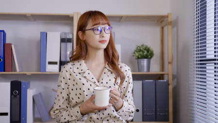 portrait happy asian woman ceo is enjoy having morning tea near window, looking into distance with a smile.