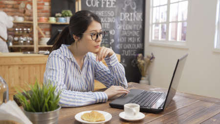 Businesswoman use laptop at modern cafe bar. Young beautiful girl freelance sitting in cozy coffee shop and working on notebook computer with cup of tea and croissant on table. waitress in background