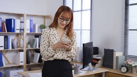 asian chinese woman manager in fashion blouse standing back against office desk is smiling while texting on phone.