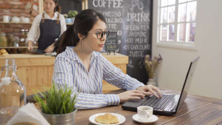 Young business woman sitting at table and taking notes in notebook computer. elegant office lady in glasses before work using laptop in breakfast time in morning cafe. barista prepare meal in counter