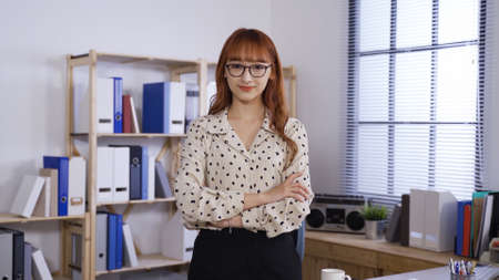 confident asian korean businesswoman wearing glasses and smiling at camera while standing with arms crossed in the office. Reklamní fotografie