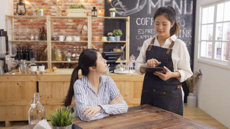 beautiful young waitress taking customer order using tablet computer in coffee shop. smiling office lady client listening to barista repeat her meal. cafe bar staff girl noting down menu on touchpad.