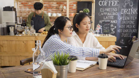 young girls colleagues having discussion while make report using laptop in cafe interior. two office lady coworker working together on notebook computer in coffee shop. asian man bartender in counter