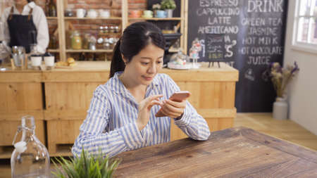 Gorgeous female reading news via network on mobile phone while waiting for order in modern coffee shop. asian woman searching information on cellphone while sit in restaurant. barista work in counter Reklamní fotografie