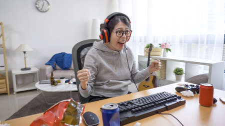 happy young asian chinese woman indoorsy in headphones with hands in fist staring at winning online game page on computer monitor