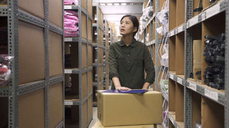Warehouse female worker in uniform pushing hand truck and delivering boxes of products at work in company stockroom. Stock Photo