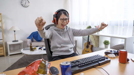 young lazy asian girl indoorsy with headphones playing video game on desktop computer and celebrating victory in bright messy living room