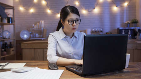 concentrated young asian korean businesswoman working on laptop computer and document at late night home kitchen.