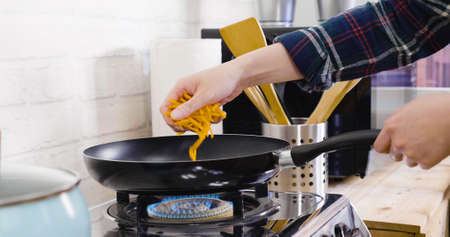 unrecognized asian woman hands holding lots of chopped carrots and puts into frying pan on gas stove. Stock Photo