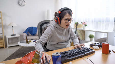 side view excited asian gamer girl in headset with microphone playing online video game on computer indoor. 写真素材