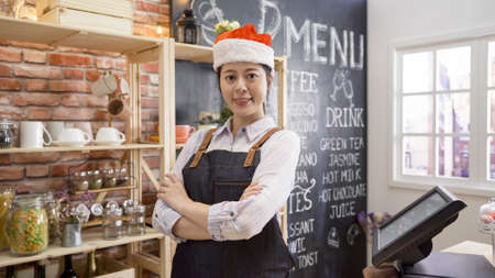 Portrait of confident young woman worker wearing apron and red santa hat standing behind cafe counter looking at camera. Foto de archivo