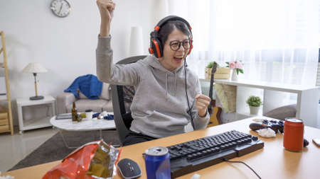 Gamer girl was super excited and raising hand after winning the esports competition of favorite video game on desktop computer.