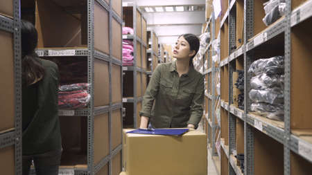 young asian japanese lady worker pushing hand truck ready for delivery in warehouse while coworker counting stock in rows of shelves.