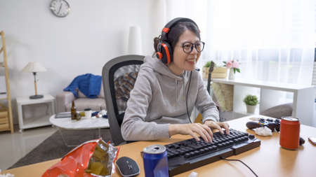 Happy asian japanese girl cheerful laughing typing on keyboard chatting with a teammate before the online game start.