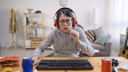 shocked asian girl holding microphone and talk online with teammate by headset at home on summer break time.