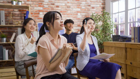 Photo of elegant pregnant listener raising hand to ask question while four asian man and women sitting on chair and taking new employee training lesson in office together.