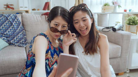 Cute pretty asian korean girls making funny selfie on smartphone with sunglasses at home by the sofa.