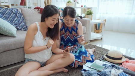 two young charming asian korean girls using credit card to book the hotel online while planning for summer travel trip at home