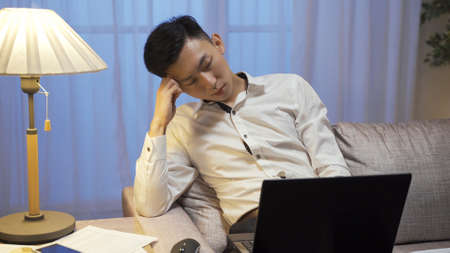 overworked asian chinese male worker is taking nap and propping head with hand while working on laptop computer on sofa in late night.