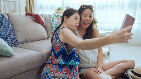 Two joyful asian chinese girlfriends taking selfie on cellphone while sitting together on floor indoors. 免版税图像