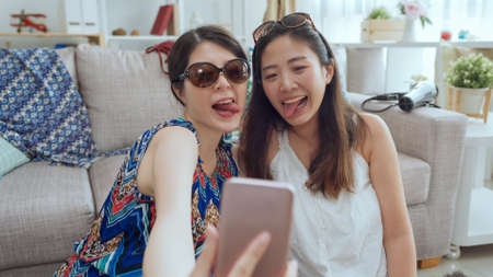 two beautiful young asian japanese sisters taking self picture on cellphone with grimacing and putting tongue out. 免版税图像