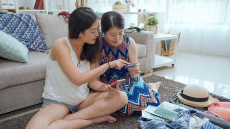 charming asian japanese female tourists using cell phone and credit card to book tickets on internet website while packing suitcase for summer vacation 免版税图像