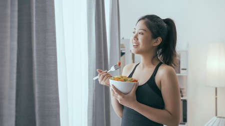 elegant asian chinese woman watching view from window and eating a bowl of healthy salad after working out at home.