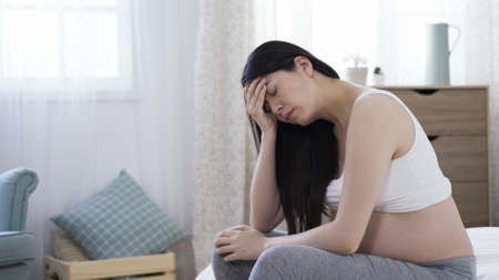 gloomy korean mother-to-be with naked abdomen sitting on bed and feeling depressed with one hand covering forehead.