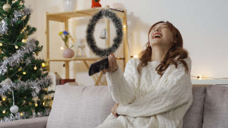 portrait of cheerful laughing asian chinese woman in white sweater holding remote control and watching tv in living room with Christmas decors in back.