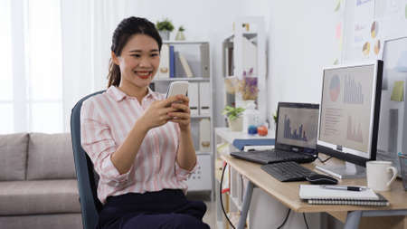 elegant asian lady freelance working at home office, joyfully checking message with good news on smart phone in early morning. Zdjęcie Seryjne