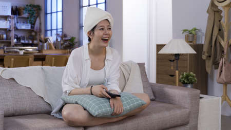 cheerful laughing asian japanese lady after shower is watching a comedy on television while sitting on comfort couch at home.