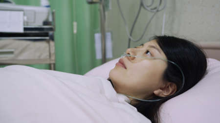 closeup asian chinese woman patient infected with conoravirus and receiving treatment in isolation is lying awake on bed in sorrow