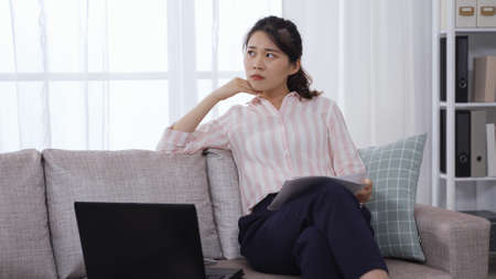 confident asian female ceo with paper and laptop looking outside while working at home office on sofa