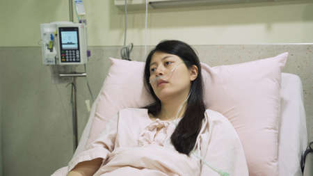 severely ill asian girl patient leaning against pillow is feeling weak and seems to be in a trance while stay in hospital alone.