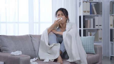 korean woman with infection touching sore throat and head hurts sitting on couch while using warm blanket covered body.