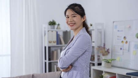 confident asian female manager in professional blazer smiling facing camera is standing with arms crossed in modern office. Zdjęcie Seryjne