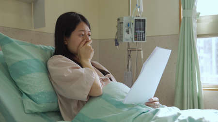 asian pregnant female patient covering mouth wearing grave expression is astonished to know she might lose her baby while lying on hospital bed.