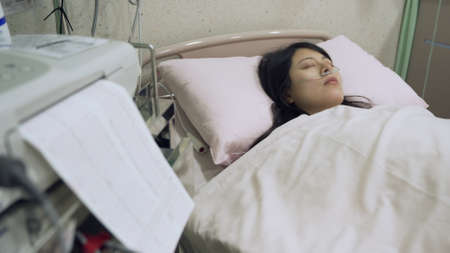 asian lady falling asleep in hospital while receiving medication of tocolytics to prevent premature labor.
